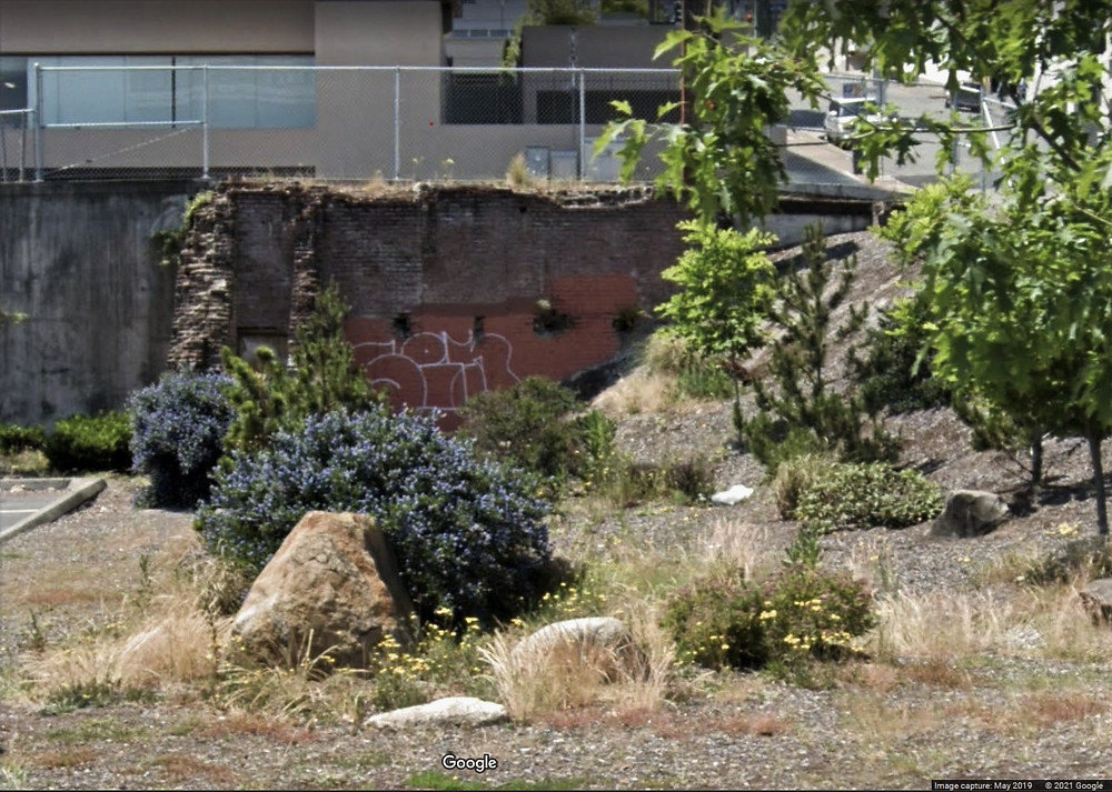 The lot of the Luzon building after it has been demolished. There is one 2-story brick wall left, with some crumbling corners from the original walls around it. The wall is tagged. Plants and rocks have been planted on the lot, but there are several weeds growing from lack of maintenance.