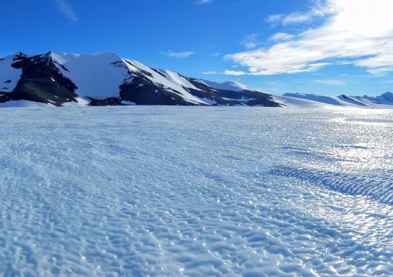 Las áreas de hielo azul son creadas por vientos feroces y de alta densidad que eliminan la capa superior de nieve y erosionan el hielo expuesto. A medida que el hielo es removido, el hielo antiguo fluye hacia la superficie, ofreciendo una visión de la historia de la capa de hielo. Imagen: AntarcticScience.cm
