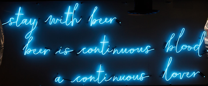 A neon sign quote from Charles Bukowski
