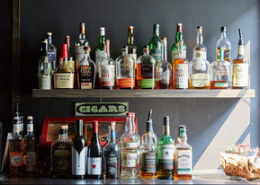 "Shelves of liquor and a sign saying ""Cigars"""