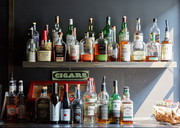 """Shelves of liquor and a sign saying """"Cigars"""""""