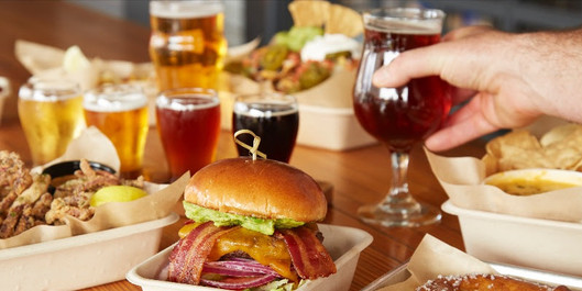 A spread of burgers, fries, and beer