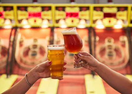 Two glasses of beer toasting in front of skeeball