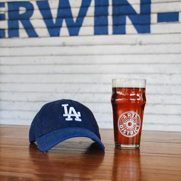 An LA Dodgers baseball cap next to a pint of beer
