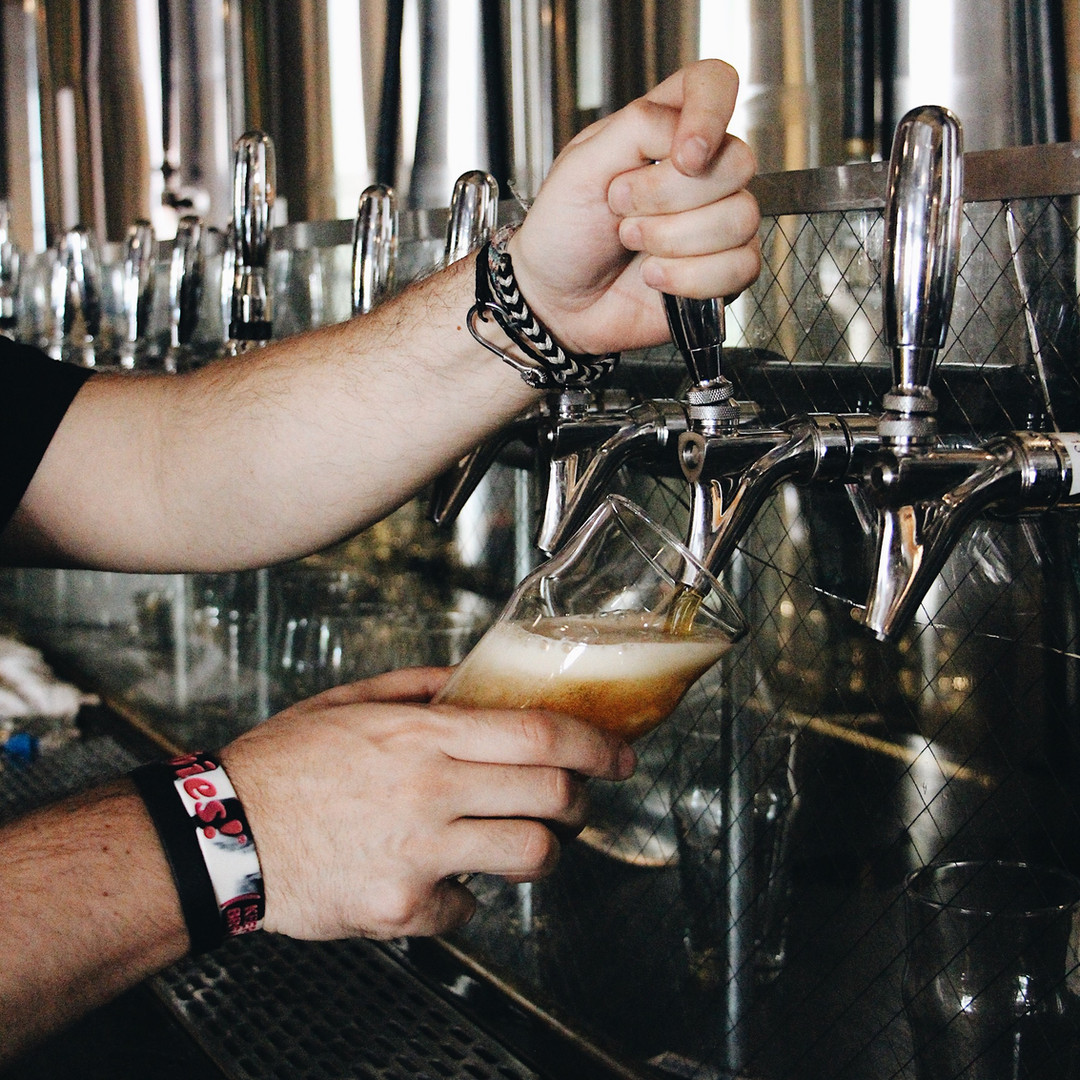 A closeup of a bartender pouring from one of the taps