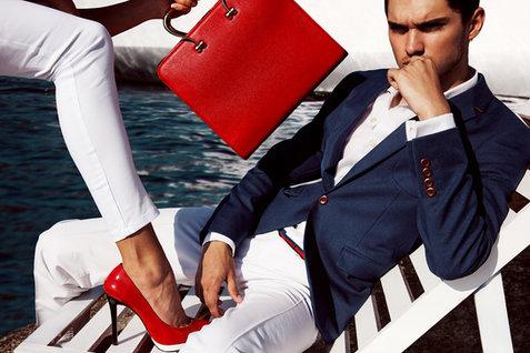 Creative fashion photographer: Stylish man wearing a blue jacket posing next to a woman holding a red handbag in Dubai Marina.