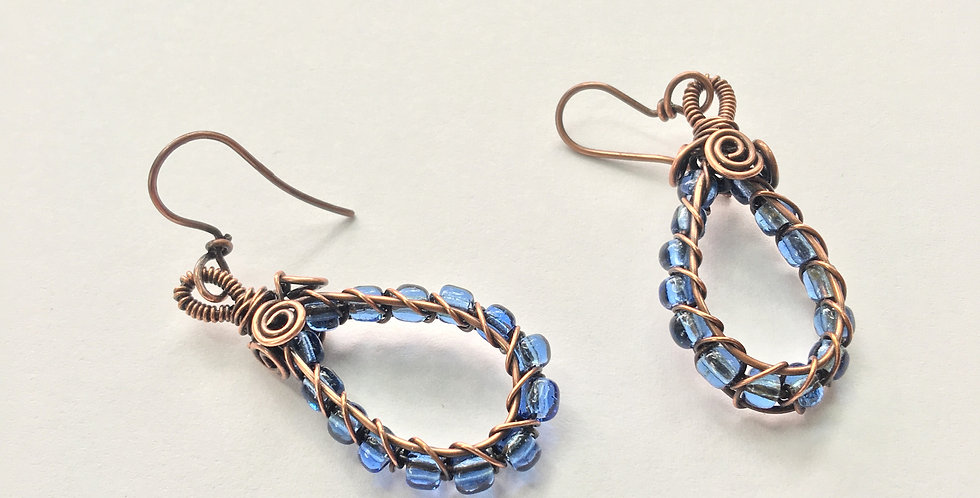 Pale Blue Beads in Copper Loop with Spirals