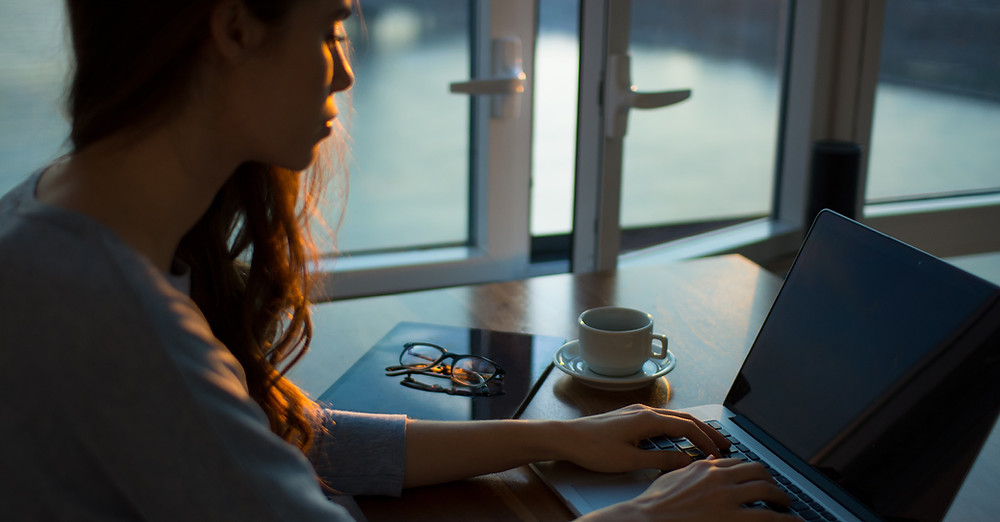 Woman working remotely with laptop and coffee cup