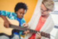 Boy learning how to play the guitar with the help of a teacher.jpg