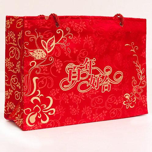 大紅色絲綢手提袋,上織繡著百年好合字樣