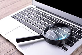 Laptop computer with magnifying glass, c
