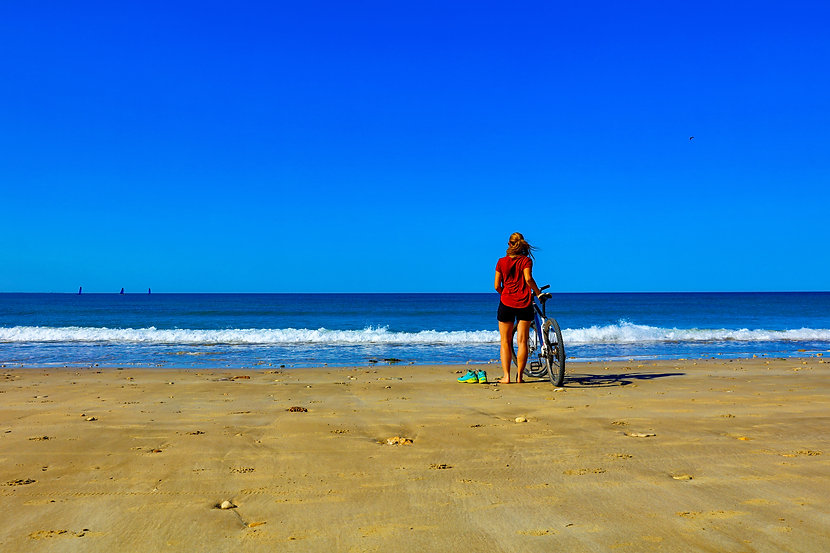 girl on bicyle on beach- freedom and hol