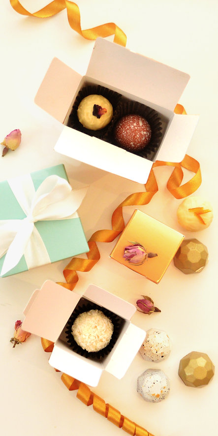 White and dark chocolate truffes, gomoulded bonbons and choclates packed in small individual wedding boxes. Arragements i decorated with tea rosses and ribbons