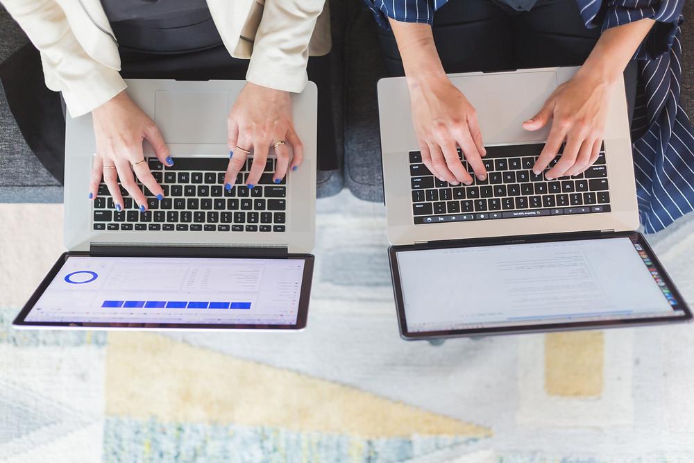 Foto tirada por cima de dois laptops colocados no colo de duas pessoas, uma ao lado da outra