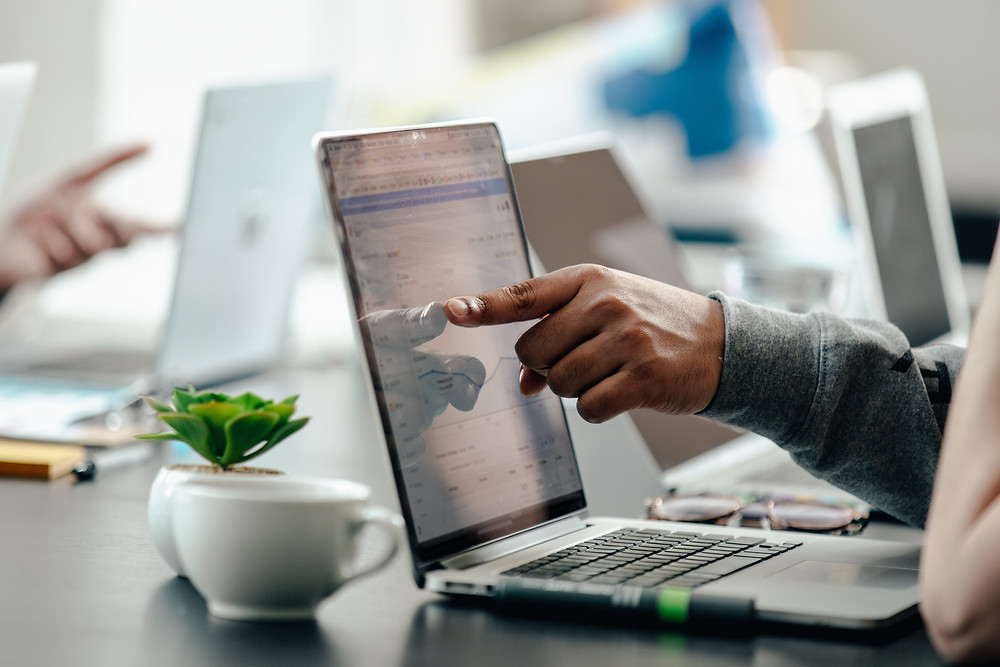 Homem apontando para o gráfico em um computador