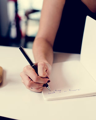hands-writing-down-a-note-on-a-notebook-