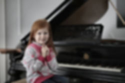 girl-in-gray-and-pink-jacket-playing-pia