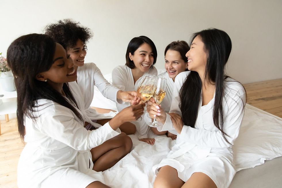 Happy diverse bridesmaids congratulating Asian bride at hen party, five beautiful young wo