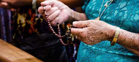 Senhora com terço na mão, link para a página de pedidos de oração.