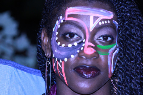 model wearing tribal face paint at an outdoor arts event