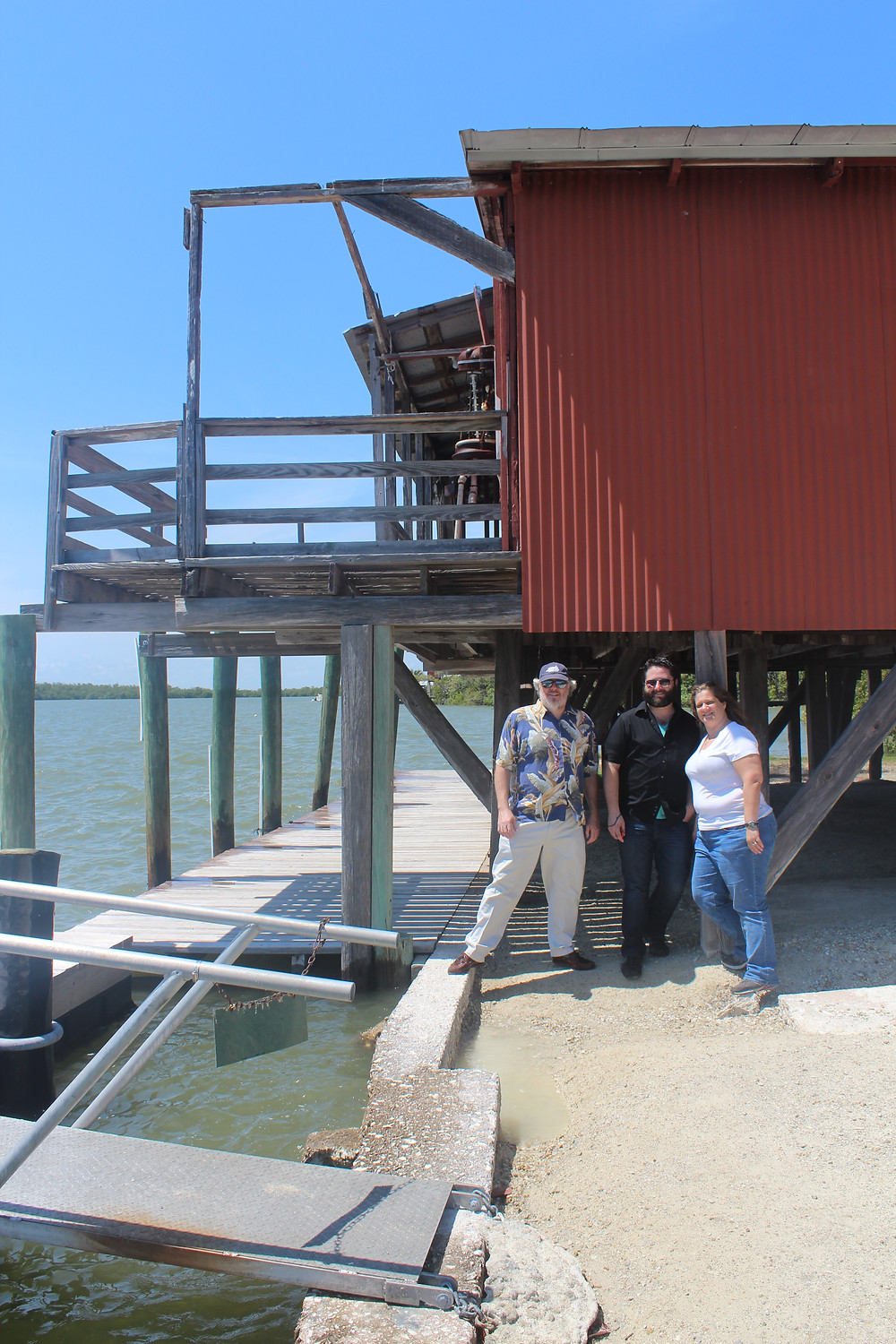 David, Joesph and Margaret pose next to the dock side of the Smallwood Store
