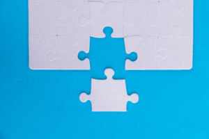 The last piece of jigsaw puzzle on a blue background.