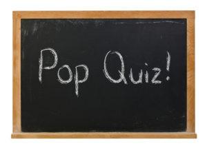 Pop Quiz written in white chalk on a black chalkboard.