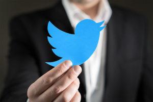 A man holding a Twitter logo.
