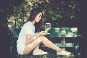 A girl on her phone on a bench.