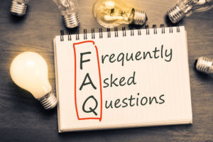 Frequently Asked Questions written in a notebook with many light bulbs in the background.