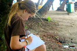 Student writes on the beach in Samara, Guanacaste, Costa Rica