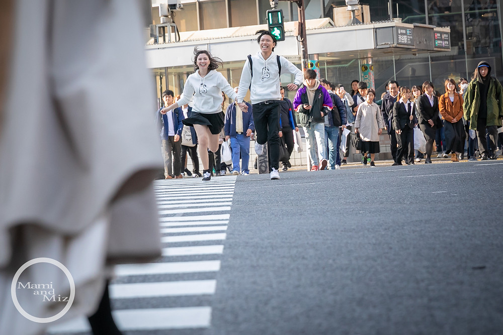 young couple running shibuya intersection