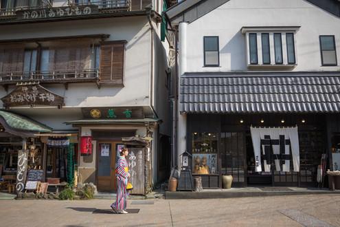 修善寺の干物屋さんの前を歩く着物の女性