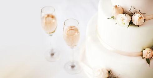 テーブルの上にウェディングケーキとシャンパンフルート
