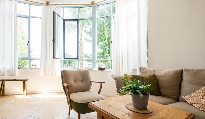 אדריכלית אלונה נבו סידי חלון גדול אור טבעי פרופיל תכלת חלון מעוגל אבן טבעית סלון