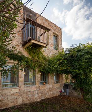 אדריכלית אלונה נבו סידי בית אבן טבעית אור טבעי דלת תכלת כניסה לבית פרגולה מעץ