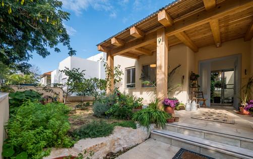 אדריכלית אלונה נבו סידי בית טיח חול חזית סימטרית פרגולה מעץ כניסה לבית
