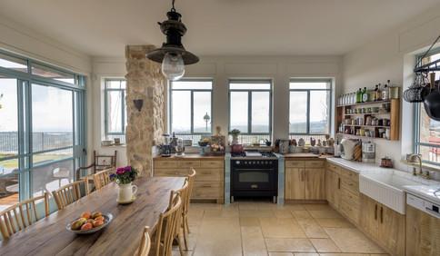 אדריכלית אלונה נבו סידי מטבח כפרי עץ אלון רצפת אבן טבעית חלונות תכלת