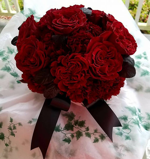Wedding bouquet with maroon carnations and black ribbon.