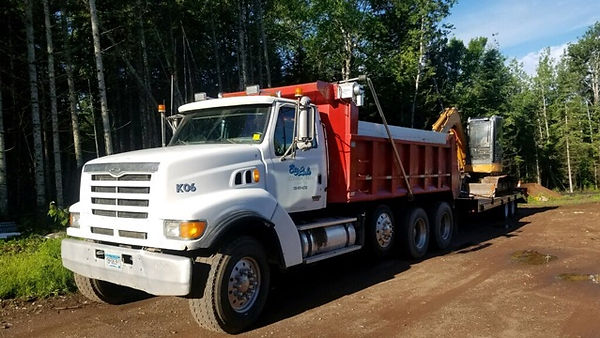 Dump truck hauling dirt and excavating equipment