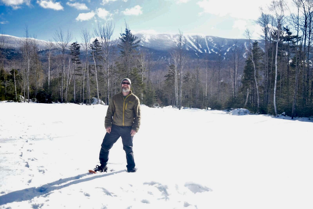 The author snowshoeing at Rangeley Lakes Trails Center, with Saddleback Mountain in the background.