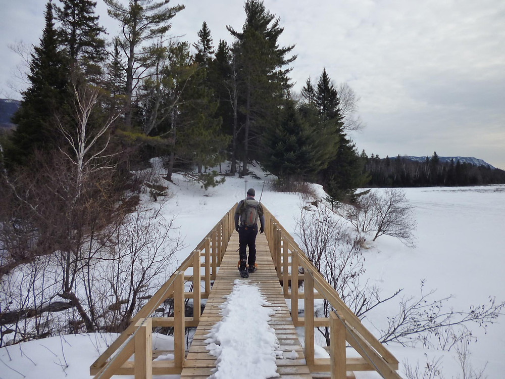 The author crossing a bridge while snowshoeing in the Bigelow Preserve.