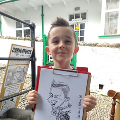 Luke Warm Caricaturing at boy On the Spot outdoors in Clovelly