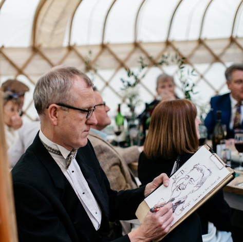 Luke Warm drawing caricatures at a wedding breakfast in a yurt