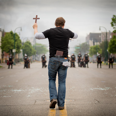Man with cross in front of riot police in Minneapolis during George Floyd protests