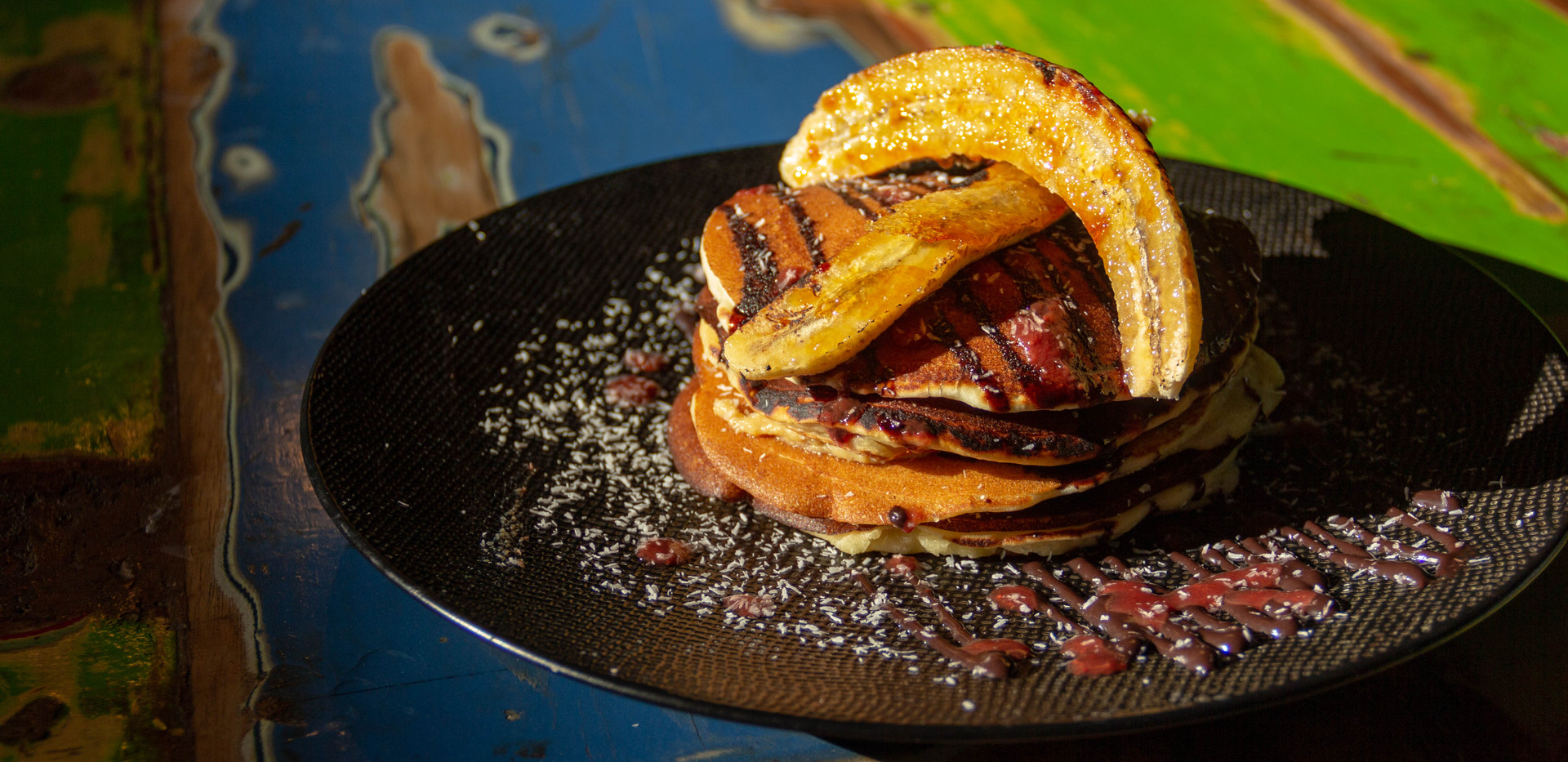 Breakfast : Caramelized Banana on top of Pancakes filled with spiced banana puree,chocolate sauce and coconut cream