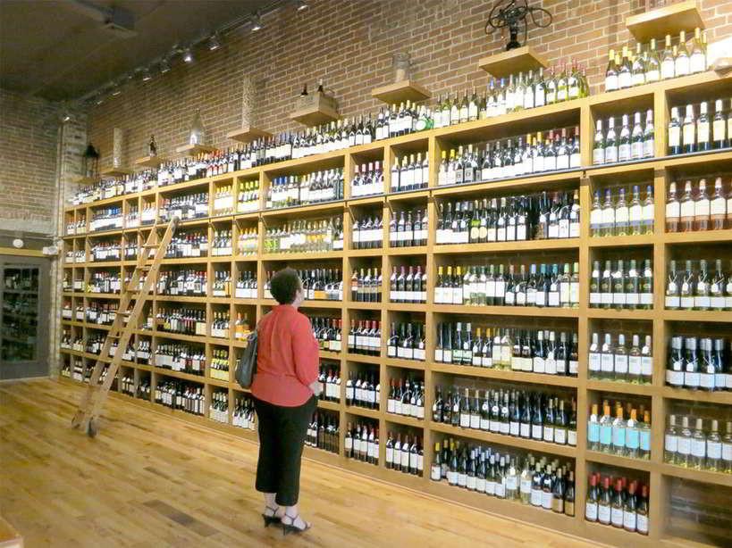 mulher olhando uma prateleira cheia de opções de vinhos