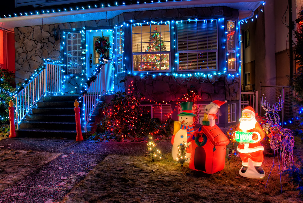 Christmas decorations in front of a lit up house.