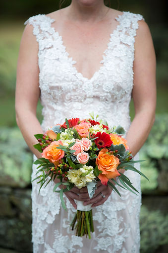 A bride holds a colorful bouquet of flowers.