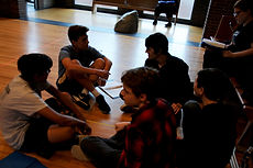 Actors sitting in a circle socializing before rehearsal begins.